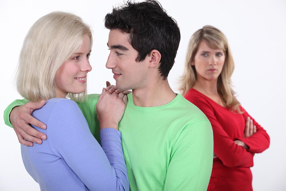 Jealous woman looking at a man hugging a young woman